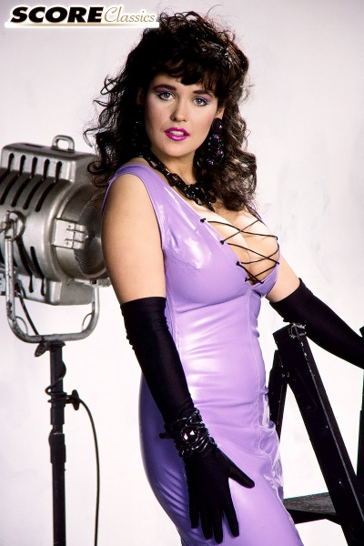 Tracey-Neve-Big-Tits-Strapped-into-Purple-Latex-Dress-002