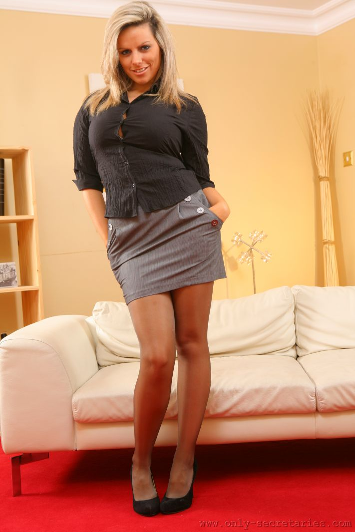 Kate C busting out of her tight, black blouse and flashing some leg in her smart, grey miniskirt.